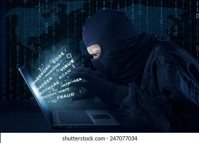 Side view of unknown hacker with mask stealing information from laptop computer