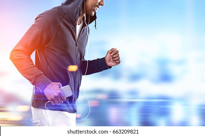 Side view of an unrecognizable African American jogger wearing a dark hoodie and white shorts running through a blurred city. Mock up toned image