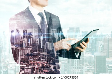 Side view of unrecognizable businessman using tablet on bright Kuala Lumpur city background with business chart grid. Network and finance concept. Double exposure