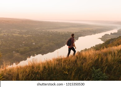Side view of unrecognizable man with backpack admiring majestic view of river while walking in wonderful countryside during sunset