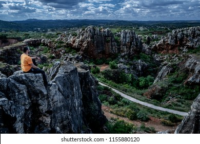 Side view of unrecognizable man sitting on top of cliff and looking away while relaxing in nature in Cerro del Hierro, Seville