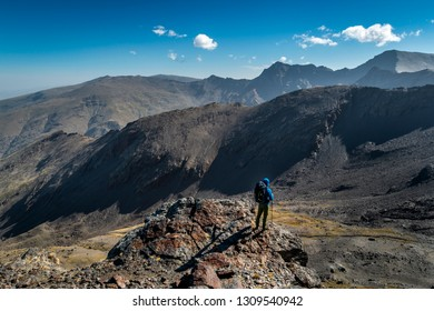 Side view of unrecognizable mountain climber with backpack standing on cliff and looking at magnificent mountains on sunny day