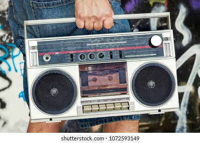 Side view of unrecognizable person carrying vintage cassette boombox.
