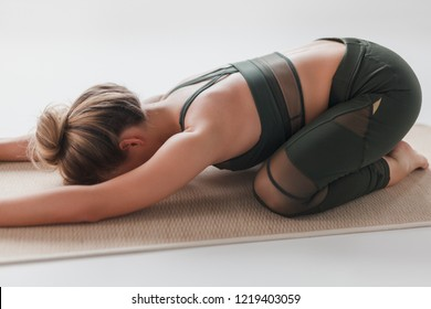 Side view of unrecognizable young female in sportswear lying on stretching mat in Extended Child's pose on white background