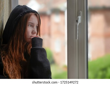 Side view of upset female teenager in black hoodie with red long hair depressed by secret abuse while standing next to window at home under isolation
