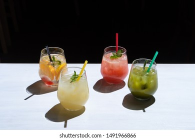 Side view of various of refreshing summer lemonades: classic lemon soda, strawberry lemonade, ginger spicy lemonade and estragon soda served on a white background