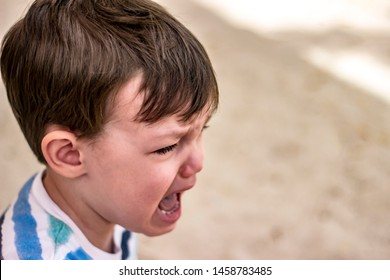 Side view of very upset three years old boy crying. Little boy crying, close up. Cute toddler crying at playground. Portrait of sad baby boy sitting down and crying. Copy space.