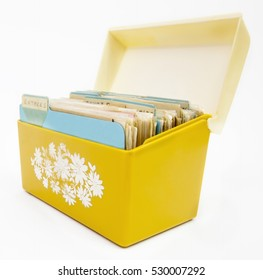 Side view of vintage 1970s yellow plastic recipe box with lid open.