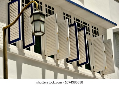 Side view of vintage wooden shutters on the exterior of a row of heritage Peranakan or Straits Chinese shophouses and an antique street lamp in bright sunlight in Chinatown Singapore.