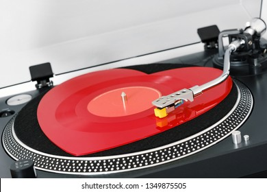 Side view vinyl turntable red heart-shaped vinyl record needle, on white background close-up. Stylus with needle DJ vinyl player. Valentine's Day. Love symbol. Popular Disco Trends 60s, 70s, 80s, 90s