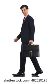 side view of a walking business man with suitcase looking at the camera on white studio background