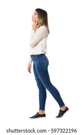 Side view of walking casual beauty in jeans talking on the phone looking away. Full body length portrait isolated over white background.