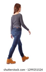 side view of walking woman. beautiful girl in motion. backside view of person.  Rear view people collection. Isolated over white. A young girl in jeans and mountain boots slowly passes by.