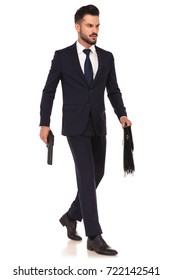 side view of a walking young elegant assasin holding gun and briefcase on white background