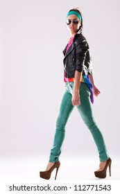 side view of a walking young woman wearing casual clothes, jacket and high heels and looking at the camera