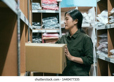 side view warehouse female worker puts cardboard box on shelf. woman employee working in storehouse and place parcels. elegant girl staff in uniform carrying heavy carton container in stockroom.
