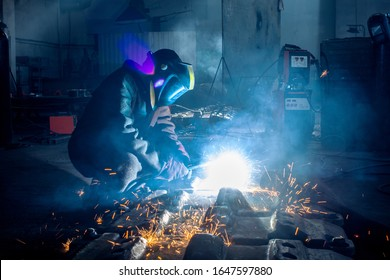 Side view of welder in protective helmet welding metal detail with sparks at factory