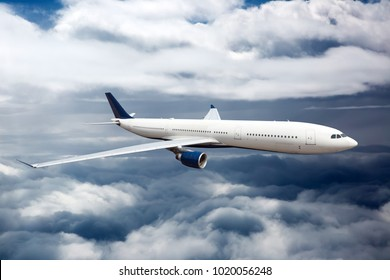 Side view of white aircraft in flight. The passenger plane flies high between the clouds layers.