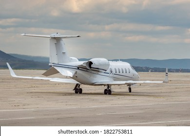 Side view of white business jet with turbofan engines at the airport. Modern technology in fast transportation, business travel and tourism, aviation concept.