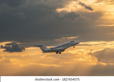 Side view of white business jet with turbofan engines. Attractive orange cloudy sunset sky over the airport. Modern technology in fast transportation, business travel and tourism, aviation.