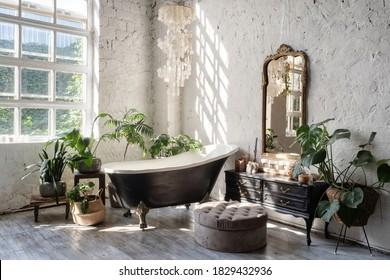 Seitliche Aussicht auf weißes, gemütliches Badezimmer mit schwarzer Wanne, klassisches Holzkommode, Spiegel, Dekoration, Pflanzen und Inneneinrichtung im schicken Boho-Stil. Konzept des komfortablen und dekorierten Zimmers zu Hause