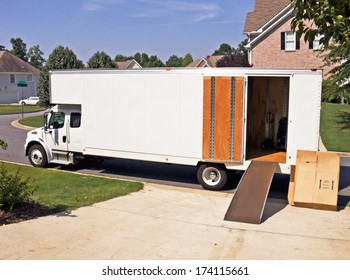side view of a white moving and storage truck with an open door and cardboard boxes stacked against the side.