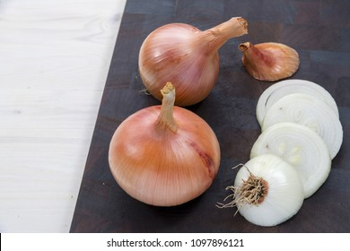 side view of white wooden table with black cutting board in diagonal with two organic onions in one piece, one onion cut in circles with one piece with roots on and one piece with dried leaves,