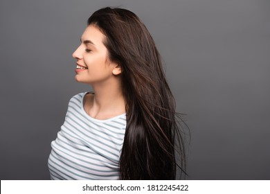side view of wind blowing through hair of brunette woman with closed eyes isolated on black