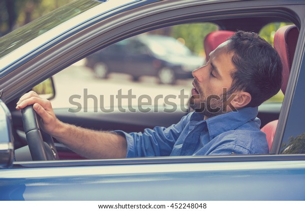 Side view window sleepy tired fatigued exhausted young man driving his car in traffic after long hour drive. Transportation safety sleep deprivation accident concept