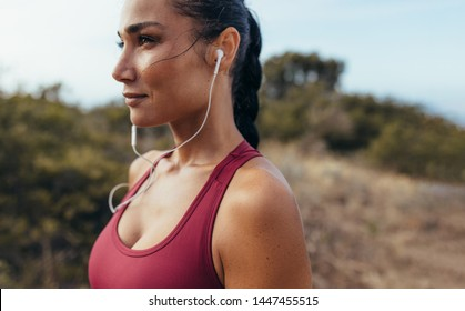 Side view of a woman athlete with earphones standing outdoors before a run. Female runner listening to music during morning workout.