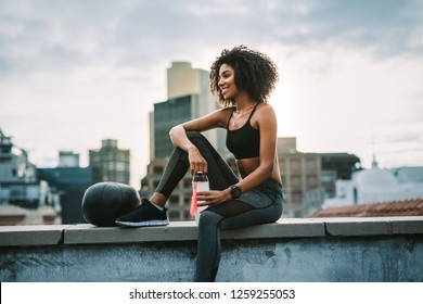 Side view of a woman athlete sitting on rooftop fence with a medicine ball drinking water after workout. Smiling woman in fitness clothes relaxing after workout sitting on rooftop.