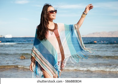 Side view of Woman in beachwear and sunglasses which walking on the beach