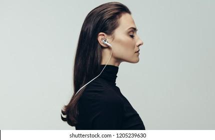 Side view of woman in black dress wearing earphones with eyes closed. Woman wearing earphones against grey background.
