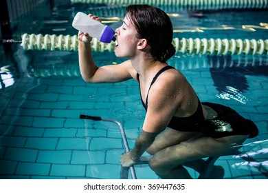 Side view of woman cycling in the pool while drinking water