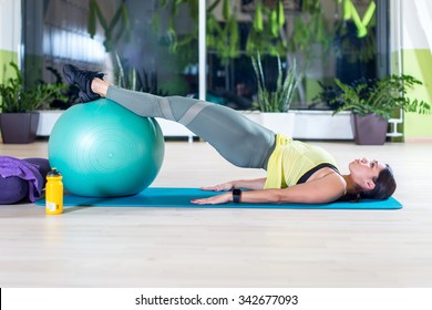 Side view of woman doing half bridge pose in fitness studio practices piltes or yoga warming up exercises for spine, backbend, strengthening back muscles.