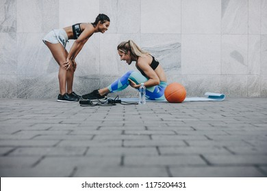 Side view of woman doing sit ups while her friend relaxes with hands on knees. Two fitness women in happy mood while training outdoors.