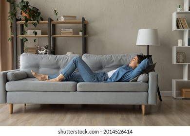 Side view woman enjoy day nap on comfy sofa. Young caucasian female put hands behind hear lying on cushion on cozy couch breath fresh conditioned air inside modern living room. Leisure, repose concept