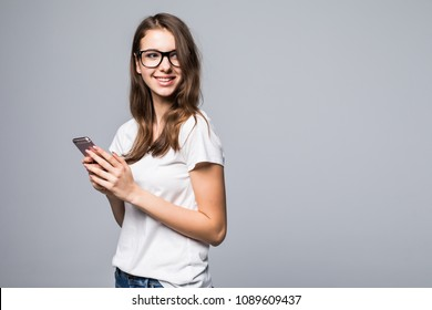 Side view of Woman in glasses and white shirt making selfie on phone. Isolated gray background
