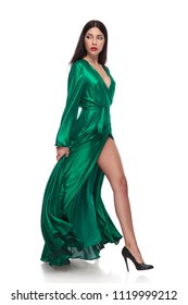 side view of woman in green dress walking on white background and looking behind, while holding the dress, full body picture