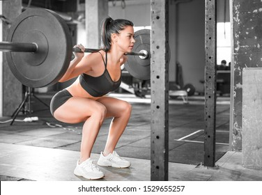 Side view of a woman in the gym. Hard training. Squats. Side-front view.