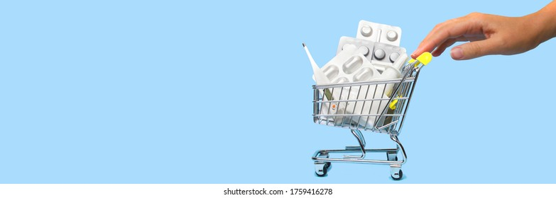 Side view of a woman hand pushing and rolling a mini shopping cart full of pills. The concept of online shopping medicine on blue background. Online Pharmacy. health insurance. Banner. Space for text