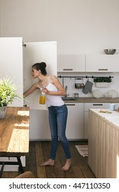 Side view of woman holding bottle of juice while looking in fridge