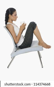 Side view of a woman holding a cup of tea and thinking on a chair