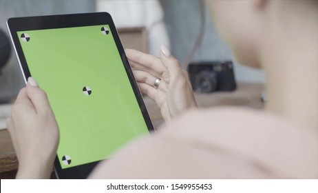 Side view of a woman holding tablet pc with green screen on wooden table background. Stock footage. Close up of a girl using Ipad with chroma key.