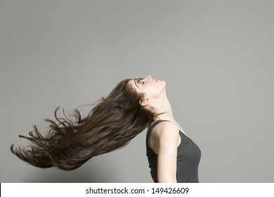 Side view of a woman with long brown hair blowing in wind against gray background