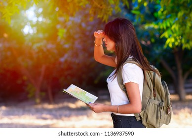 Side view of a woman looking forward at sunset outdoor. Personal Development, Attainment Motivation Career Growth Concept. Portrait of beautiful girl tourist with backpack holding travel guide book.