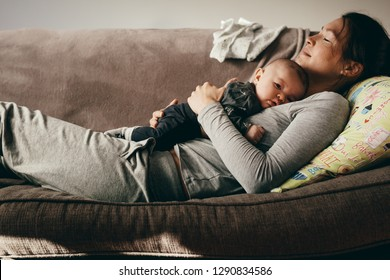 Side view of a woman lying on couch with eyes closed and holding her baby on her chest. Tired mother taking rest sleeping on a sofa with her baby on her.