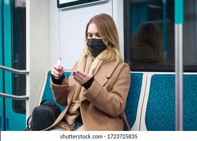 Seitenansicht der Frau in medizinischer Maske mit Telefon in ihren Händen sitzen in U-Bahn-Auto. Coronavirus-Epidemie