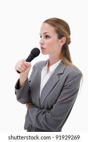 Side view of woman with microphone against a white background