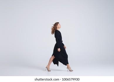 Side view of woman model walking in trend black dress